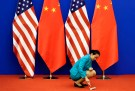 An attendent cleans the carpet next to U.S. and Chinese national flags before a news conference for the 6th round of U.S.-China Strategic and Economic Dialogue at the Great Hall of the People in Beijing, July 10, 2014. REUTERS/Jason Lee (CHINA - Tags: POLITICS BUSINESS) - GM1EA7A1AO901